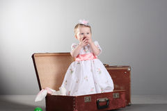 Little girl sits in a suitcase Stock Images