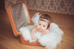 Little girl sits in a suitcase. A dark background. Royalty Free Stock Photos