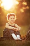 Little girl sits on sunset Royalty Free Stock Images