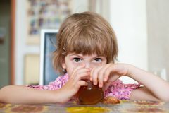 Little girl sits at table drinking tea from transparent glass Royalty Free Stock Image