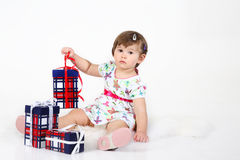 Little girl sits with three gift boxes. Stock Photography