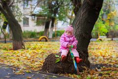 The little girl sits with an umbrella on a stub near a tree in the fall stock image