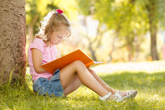 Little girl sits under a large tree at the park and reads a book Stock Images