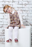 Little girl sits on white cube next to brick white wall Stock Photography