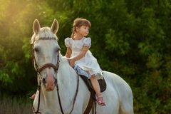 The little girl sits on a horse astride. The little girl sits on a white horse astride Royalty Free Stock Photo