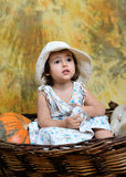 The little girl sits in a wicker basket Stock Photos