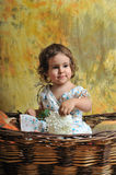 The little girl sits in a wicker basket Royalty Free Stock Photos