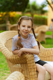 Little girl sits in wicker chair Royalty Free Stock Photo