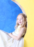 Little girl sits on a yellow moon. The girl has a beautiful golden gown. Girl blonde with a diadem in her hair. Blue background Royalty Free Stock Photography