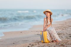 A little girl sits on a yellow suitcase on the beach royalty free stock photos