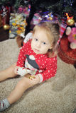 Little girl sitting against Christmas decoration Stock Photo