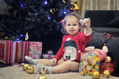 Little girl sitting against Christmas decoration Royalty Free Stock Images