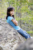 Little girl sitting against rock, smiling Stock Photo