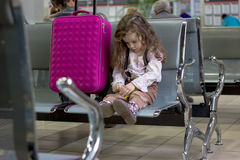 Little girl sitting in airport terminal Royalty Free Stock Photo