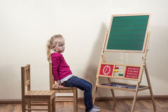 Little girl sitting alone in front of a blackboard. It is thoughtful and sad Royalty Free Stock Photo