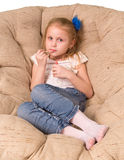 Little girl sitting in armchair isolated on white Stock Photo