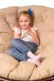Little girl sitting in armchair isolated on white Royalty Free Stock Photos