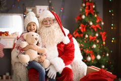 Little girl sitting on authentic Santa Claus` lap indoors. Little girl with teddy bear sitting on authentic Santa Claus` lap indoors royalty free stock photography