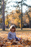Little girl sitting on autumn leaves Royalty Free Stock Image