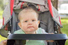 Little girl sitting in a baby carriage Royalty Free Stock Image