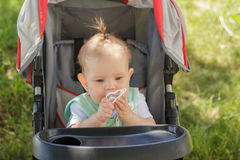 Little girl sitting in a baby carriage Royalty Free Stock Photos