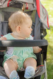 Little girl sitting in a baby carriage Stock Image