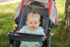 Little girl sitting in a baby carriage Royalty Free Stock Photo