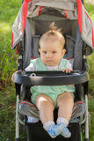 Little girl sitting in a baby carriage Stock Photography