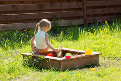 Little girl sitting back playing in sandbox Royalty Free Stock Photos