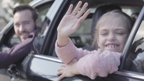 Little girl sitting on the back seat of the car waving her hand looking in camera close up. The father is on the driver. `s sit. Happy man spending time with his stock footage