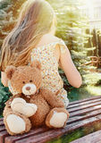 Little girl sitting back with teddy bear on the bench in sun bea Stock Photos