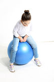 Little girl sitting on the ball. Little girl sitting on the blue rubber ball Royalty Free Stock Photography