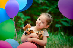 Little girl sitting in balloons Royalty Free Stock Photos