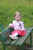 Little girl sitting on the bank, holding a bouqet of flowers Royalty Free Stock Photos