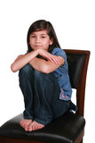Little girl sitting on bar stool. Somber expression. Part Asian-Scandinavian descent Royalty Free Stock Photo
