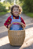 Little girl is sitting in the basket stock images