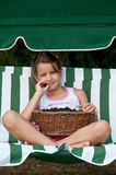 Little girl sitting with a basket of blackberries Stock Photography