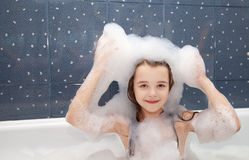 Little girl sitting in a bath with soap suds on her head. Smiling little girl sitting in a bath and imposes soap suds on her head Stock Photography