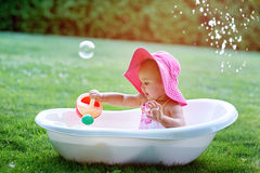 Little girl sitting in a bathtub with soap bubbles Royalty Free Stock Photo