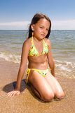 Little girl sitting at the beach Royalty Free Stock Images