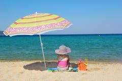 Little girl sitting on beach Royalty Free Stock Photos