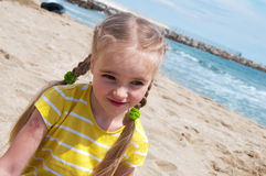 Little girl sitting on the beach Stock Photo