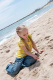 Little girl sitting on the beach Royalty Free Stock Images