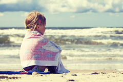 Little girl sitting on the beach Stock Photography