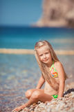 Little girl sitting on the beach near the sea Royalty Free Stock Photography