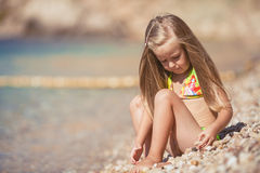 Little girl sitting on the beach near the sea Stock Photo