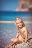 Little girl sitting on the beach near the sea Stock Photos