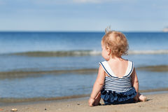 Little girl sitting on beach in swimsuit and dreams stock photo