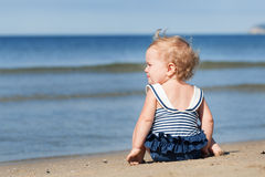 Little girl sitting on beach in swimsuit and dreams Stock Photography