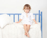 Little girl sitting on the bed. Little girl sitting on her bed Royalty Free Stock Images
